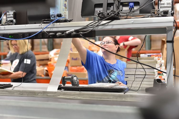 female employee works in a textbook shipping warehouse