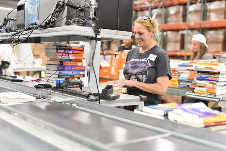 female employee works in a textbook warehouse distribution center