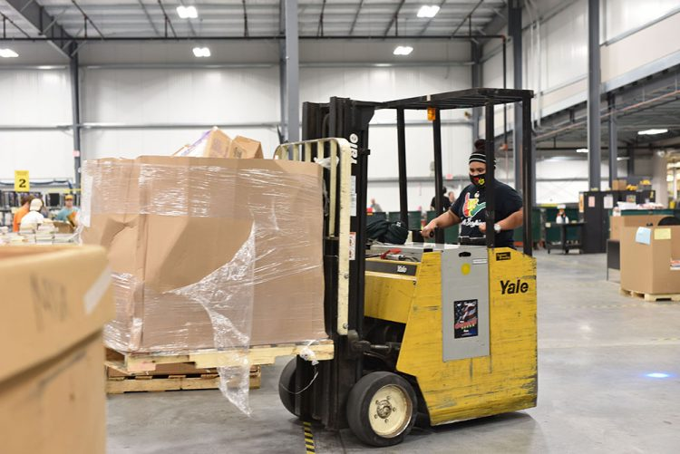 female employee drives a forklift in the distribution center carrying a large box of textbooks