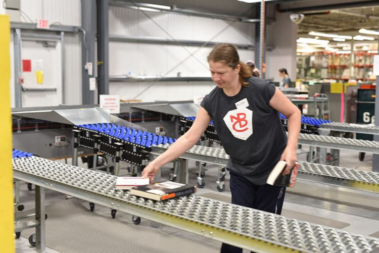 female employee puts textbooks on the line in warehouse distribution center