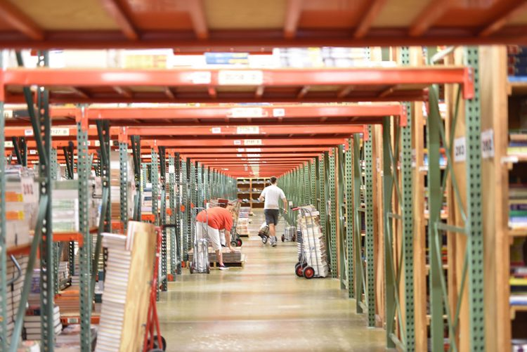rows of textbook shelves in a warehouse are stocked by two employees