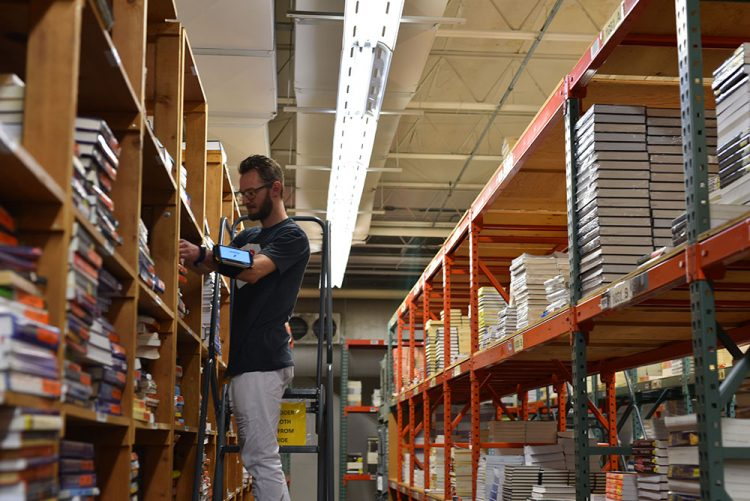 a male employee gathers textbooks for an order in a warehouse